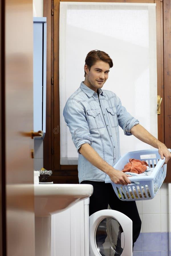 Homem que faz tarefas com máquina de lavar foto de stock