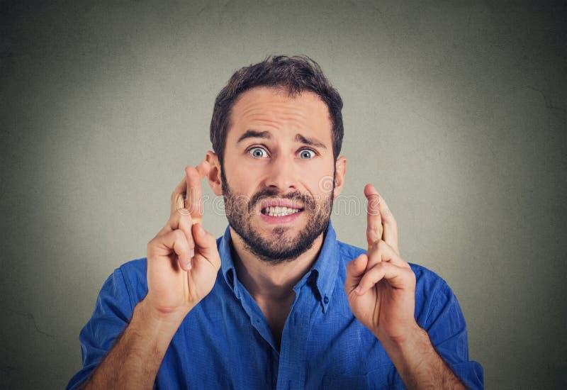 Homem que faz um desejo que cruza seus dedos fotos de stock