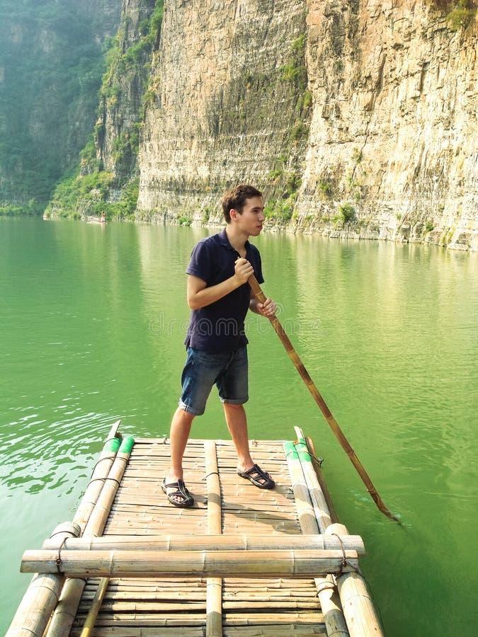 Homem que flutua em uma jangada de bambu imagens de stock royalty free