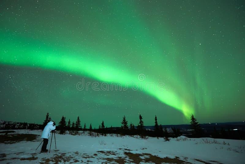 Homem que fotografa Aurora Borealis imagens de stock