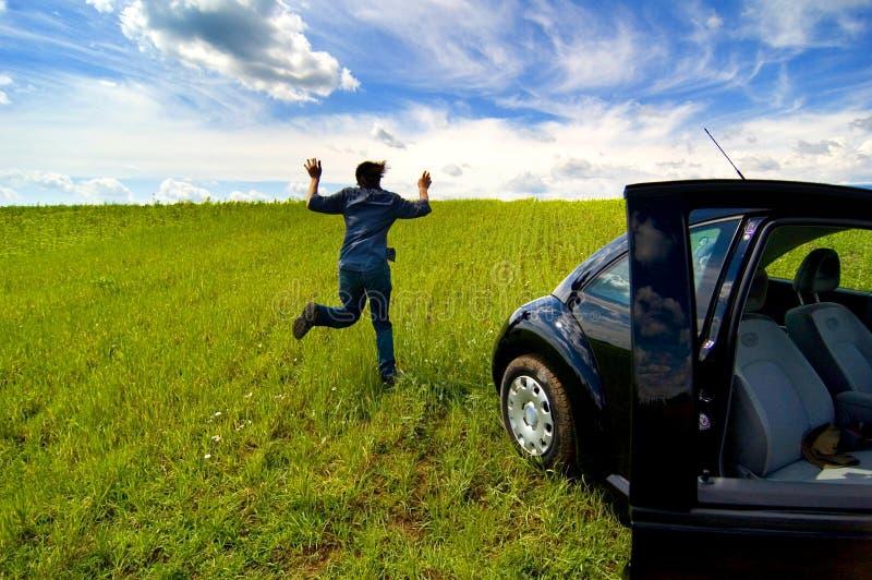 Homem que funciona do carro no campo aberto foto de stock