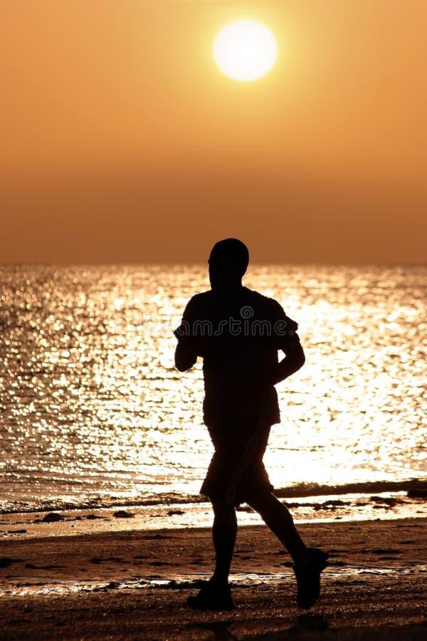 Homem que funciona na praia foto de stock royalty free