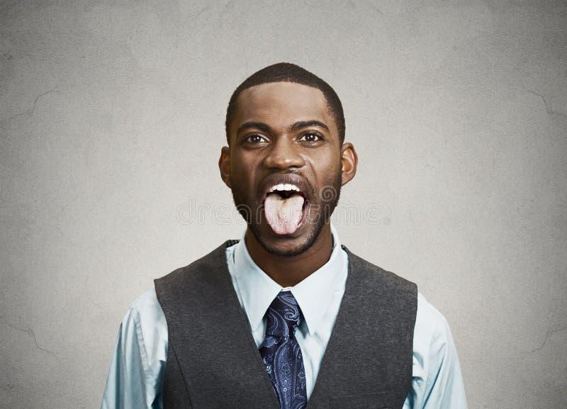 Homem que fura sua lingüeta para fora imagem de stock