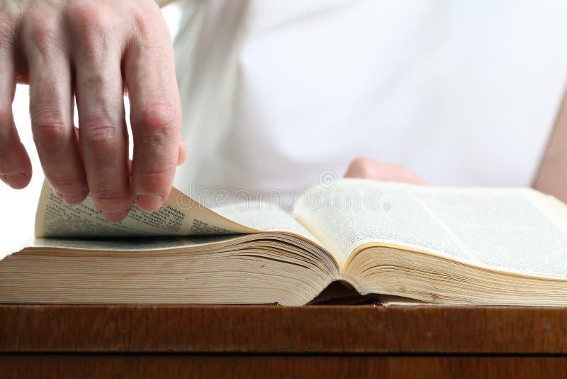 Homem que gira a página da Bíblia fotografia de stock royalty free