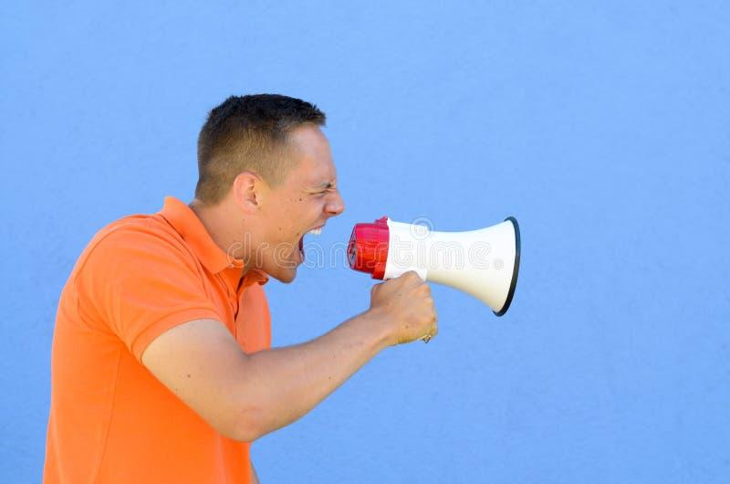 Homem que grita através do megafone imagem de stock