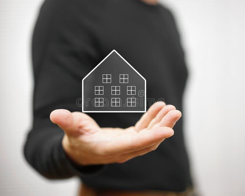 Homem que guarda a casa virtual Conceito da propriedade e dos bens imobiliários imagens de stock royalty free
