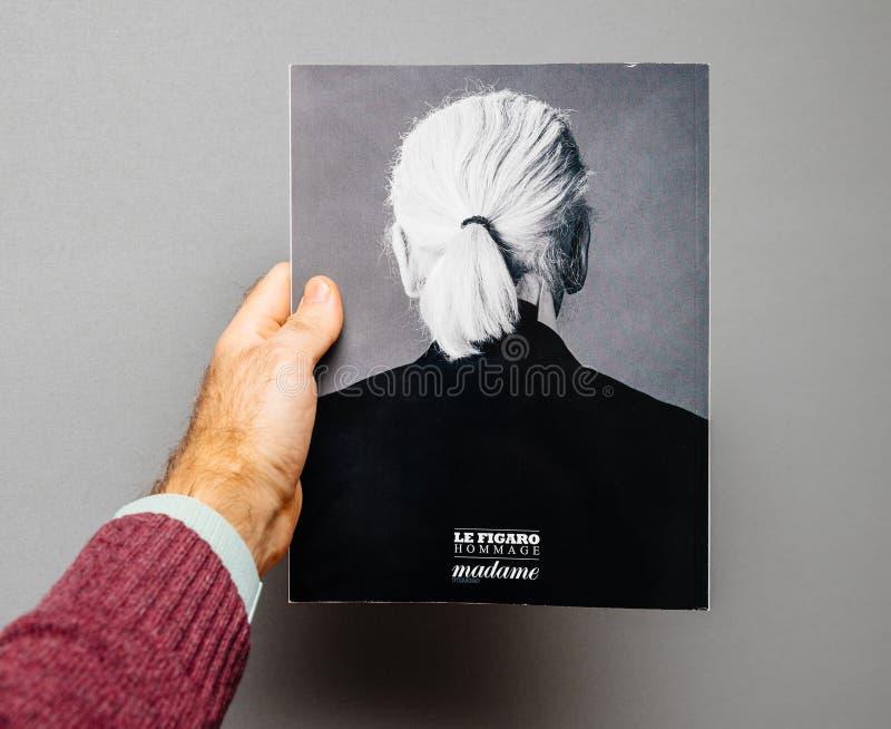Homem que guarda compartimentos Le Figaro que caracteriza a morte de Karl Lagerfeld da tampa fotografia de stock royalty free
