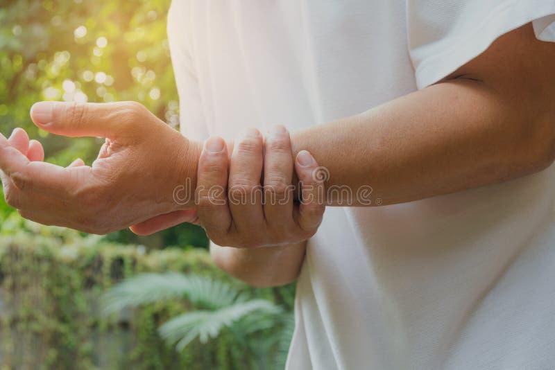 Homem que guarda a dor do pulso em um homem do pulso do homem que faz massagens w doloroso imagem de stock royalty free