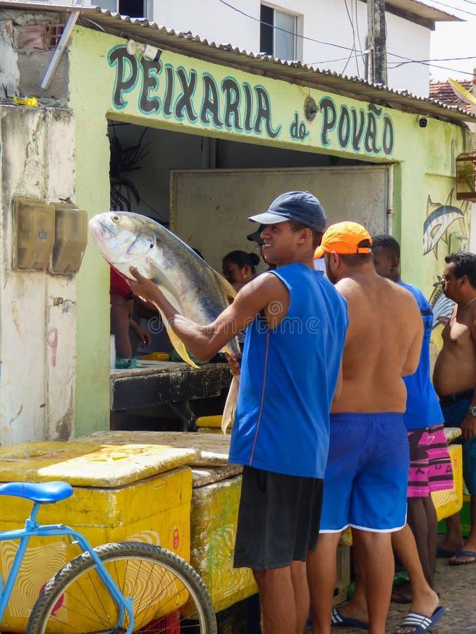Homem que guarda e que mostra um peixe grande na frente de um mercado de peixes imagens de stock