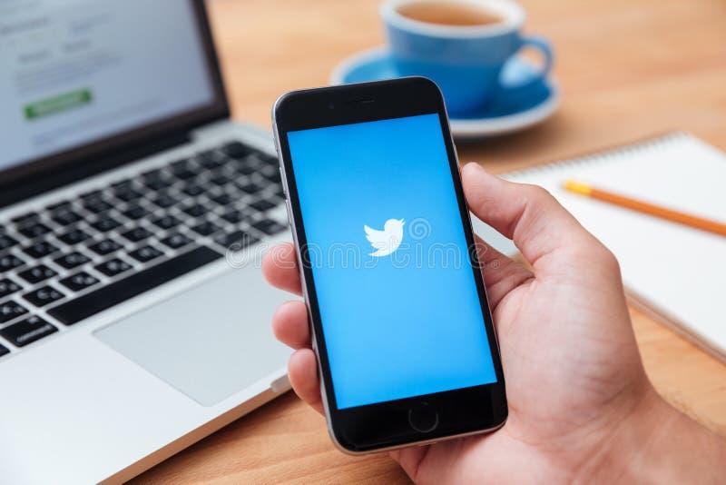 Homem que guarda a exibição Twitter app do iphone 6 foto de stock