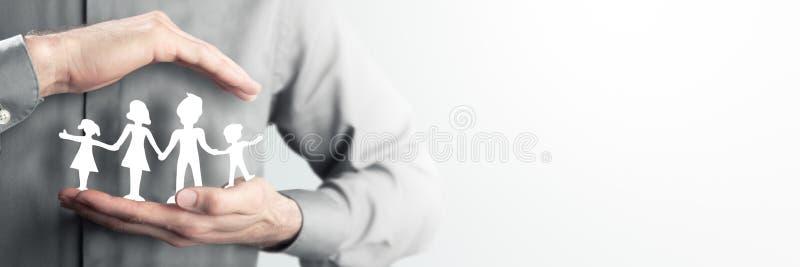 Homem que guarda a família do papel perto de seu coração fotos de stock