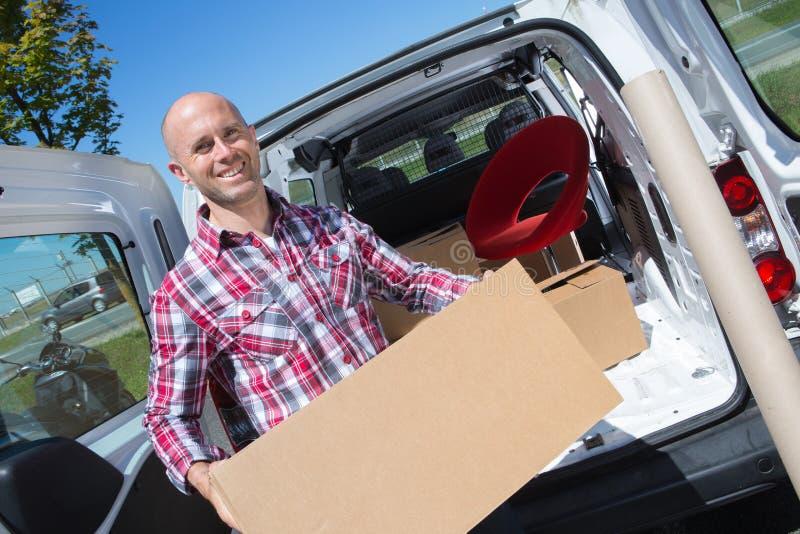 Homem que guarda a grande caixa na camionete traseira imagens de stock royalty free