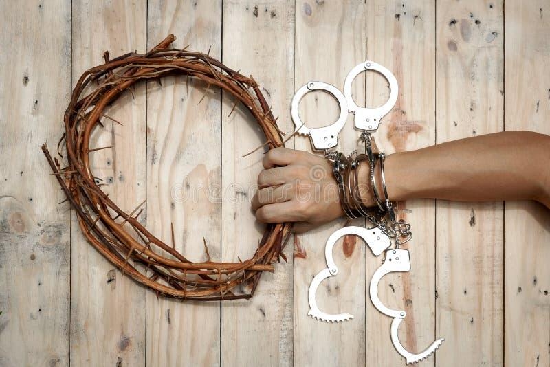 Homem que guarda Jesus Crown Thorns com sua mão e muitas algemas foto de stock