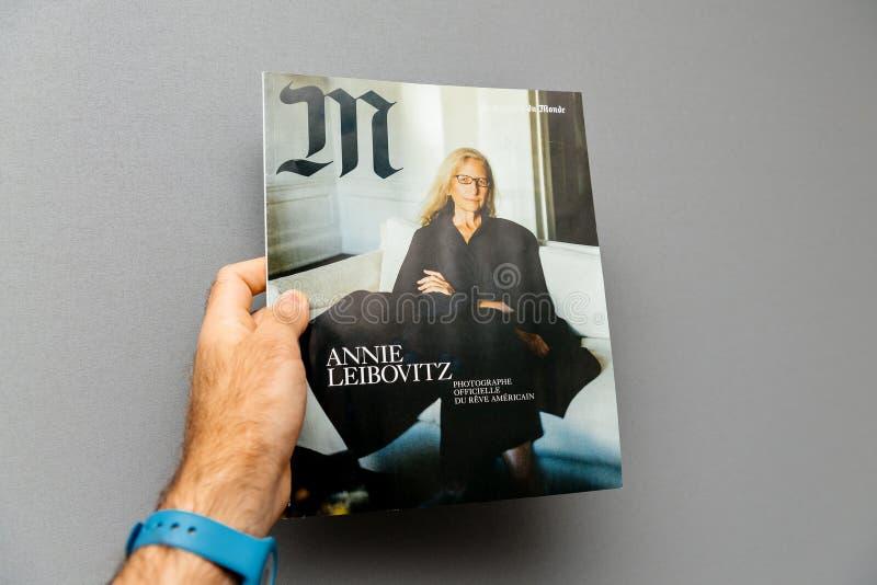Homem que guarda M Magazine Le Monde com Anne Leibovitz imagem de stock