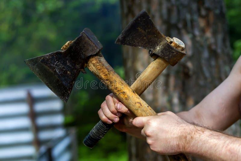 Homem que guarda machados na natureza fotografia de stock royalty free