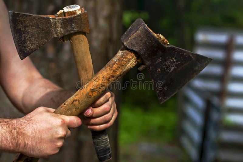 Homem que guarda machados na natureza imagem de stock royalty free