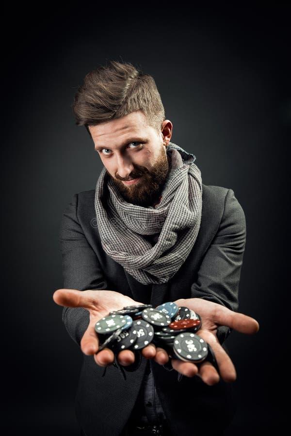Homem que guarda microplaquetas de pôquer imagem de stock