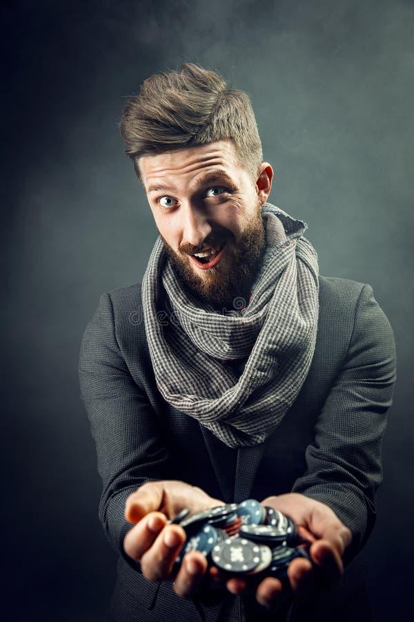 Homem que guarda microplaquetas de pôquer fotografia de stock