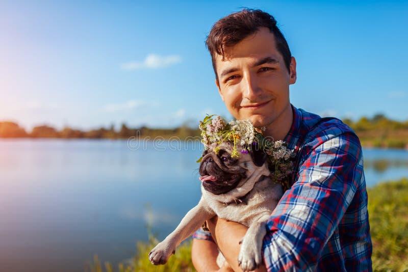 Homem que guarda o cão do pug com a grinalda da flor na cabeça Homem que anda com o animal de estimação pelo lago do verão imagem de stock