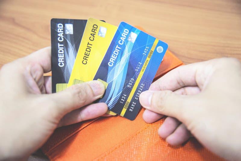 Homem que guarda o cart?o de cr?dito ? disposi??o - em linha pagando da casa ou do conceito aumentado do cart?o de cr?dito do d?b fotos de stock