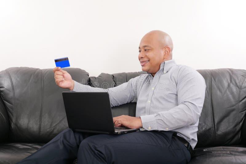 Homem que guarda o cartão de crédito fotografia de stock royalty free