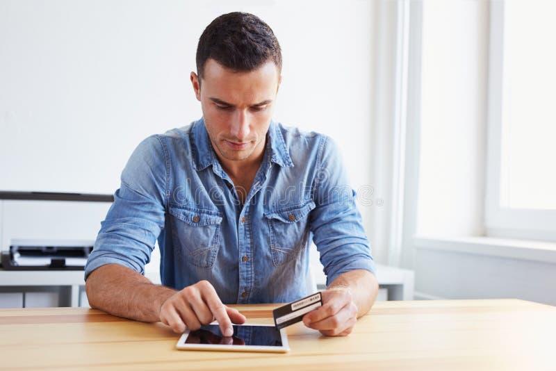Homem que guarda o cartão de crédito e a tabuleta digital fotos de stock royalty free