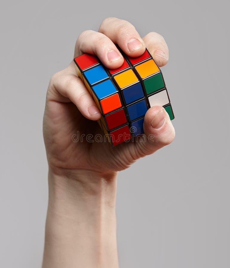 Homem que guarda o cubo do rubik em suas mãos imagem de stock royalty free