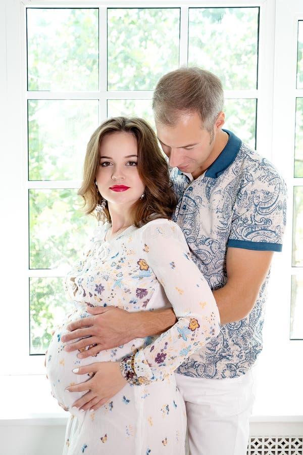 Homem que guarda o estômago da mulher gravida no quarto imagens de stock royalty free