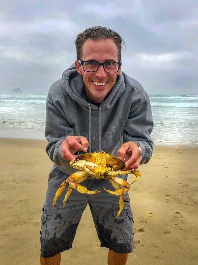Homem que guarda o grande caranguejo na praia fotografia de stock