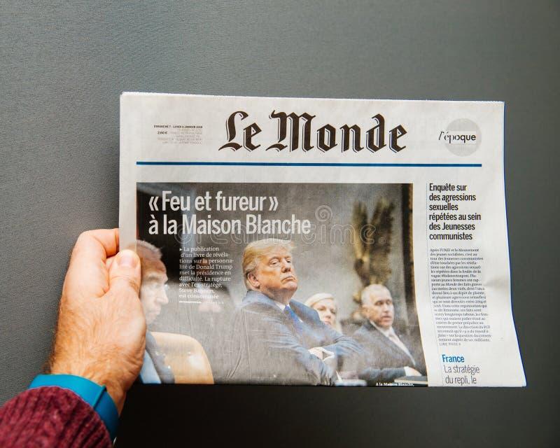 Homem que guarda o jornal de Le Monde com Donald Trump imagens de stock royalty free