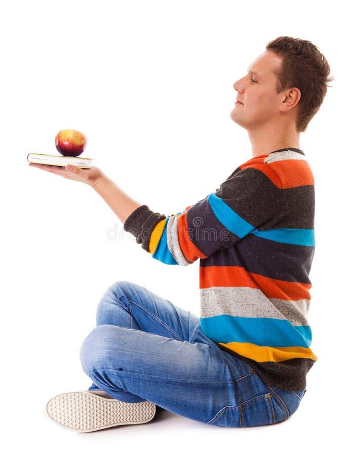 Homem que guarda o livro e a maçã vermelha. Mente e corpo saudáveis imagem de stock