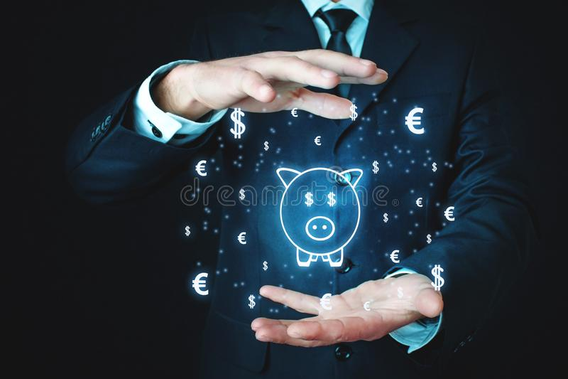 Homem que guarda o mealheiro com símbolos de moeda Conceito do investimento foto de stock royalty free