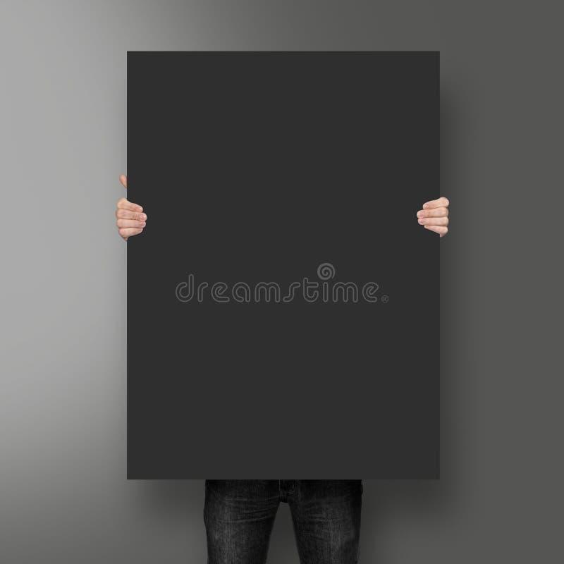 Homem que guarda o modelo preto do cartaz fotografia de stock royalty free