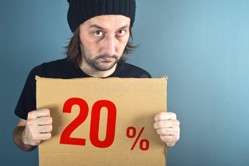 Homem que guarda o papel do cartão com preço com desconto das vendas imagens de stock