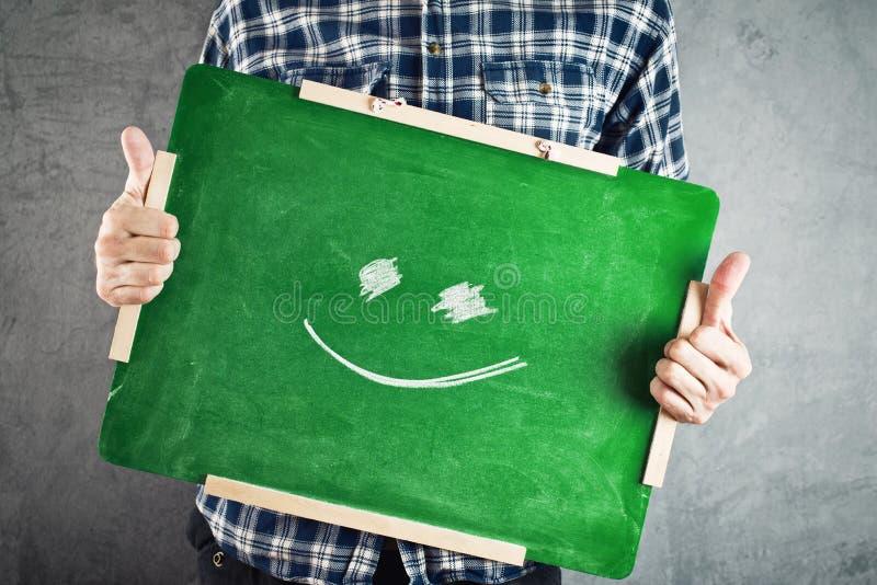 Homem que guarda o quadro verde com cara do smiley fotografia de stock