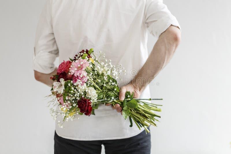 Homem que guarda o ramalhete das flores fotografia de stock