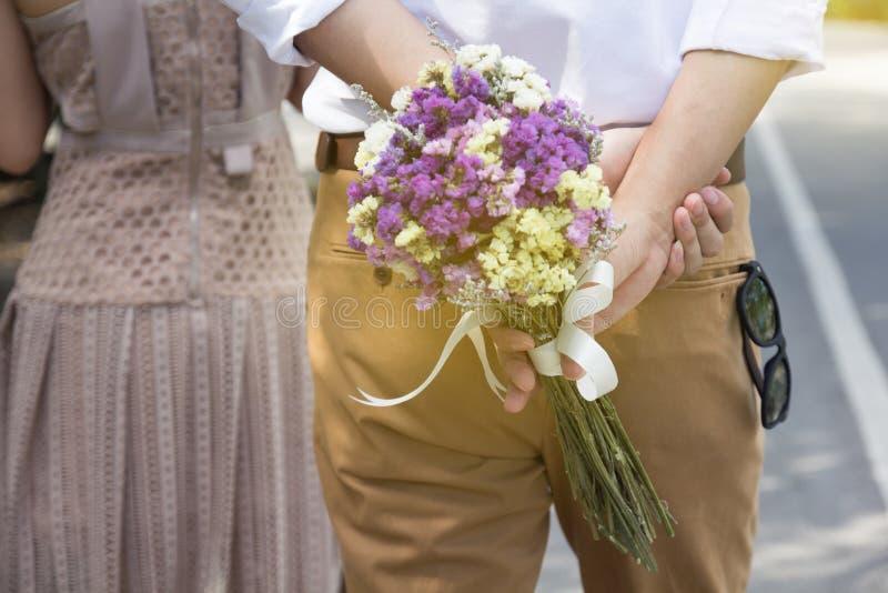 Homem que guarda o ramalhete das flores que anda atrás da mulher Dando flores imagens de stock