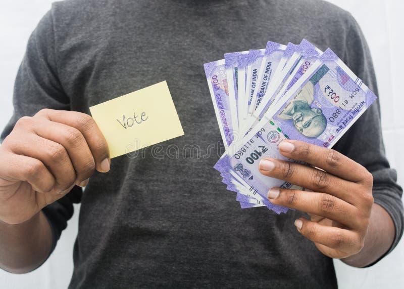 Homem que guarda o símbolo do dinheiro e do voto à disposição, conceito de mostrar um dinheiro para o voto fotografia de stock royalty free