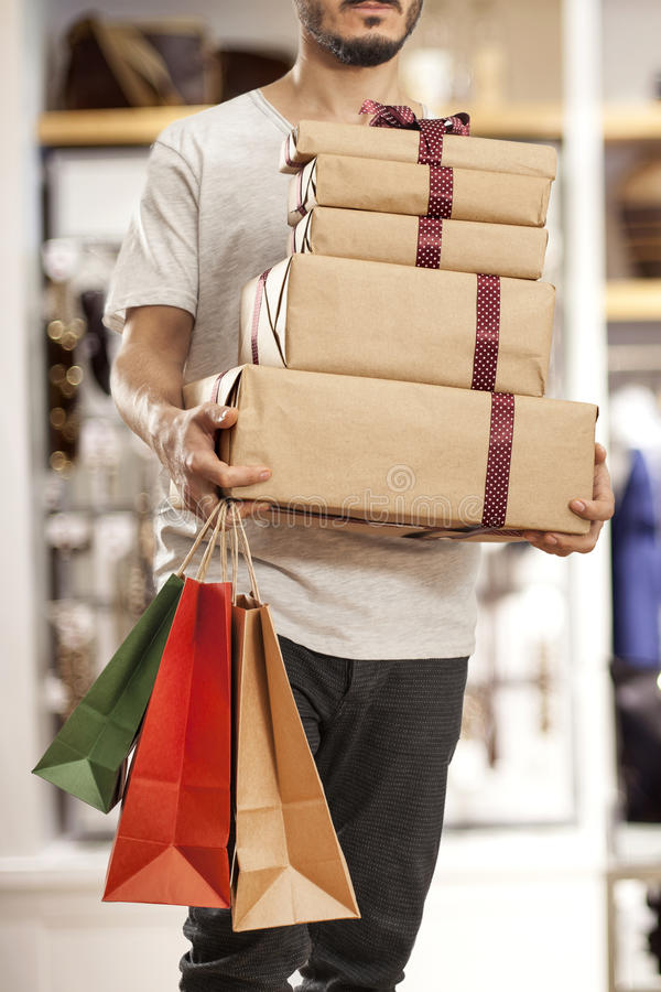 Homem que guarda o saco de compras de papel com caixas de presente fotografia de stock royalty free