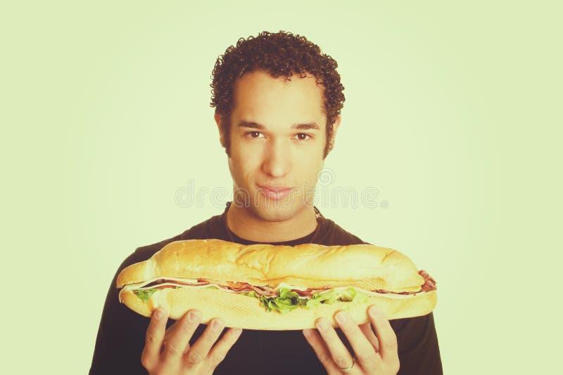 Homem que guarda o sanduíche fotografia de stock