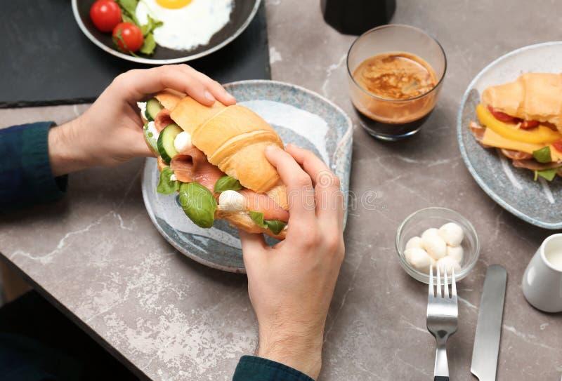 Homem que guarda o sanduíche saboroso do croissant sobre a placa imagem de stock royalty free