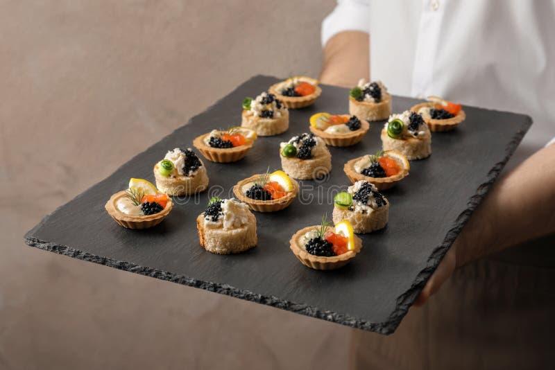 Homem que guarda a placa da ardósia com aperitivos do caviar imagem de stock royalty free