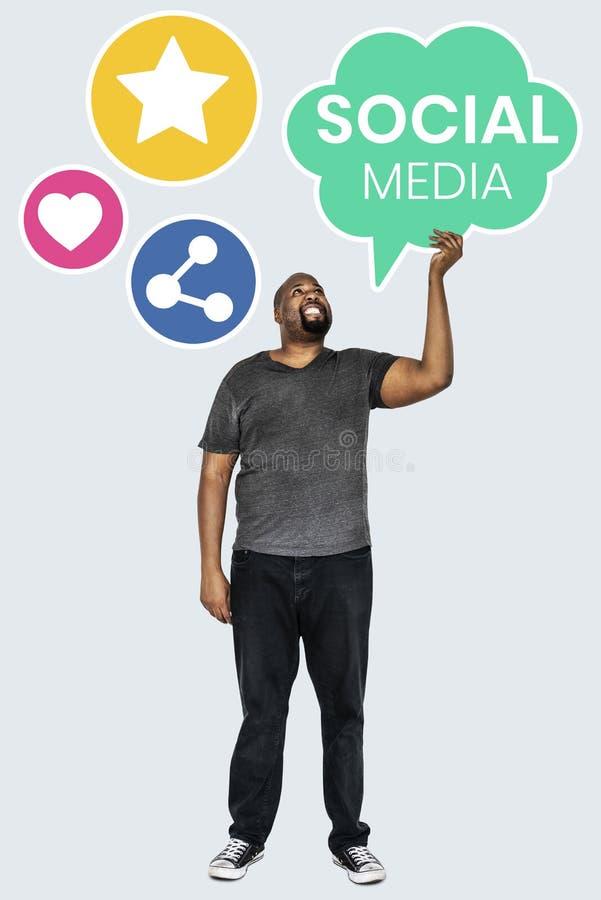 Homem que guarda símbolos sociais dos meios imagem de stock