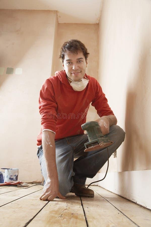 Homem que guarda a sala de Sander While Kneeling In Unrenovated imagem de stock royalty free