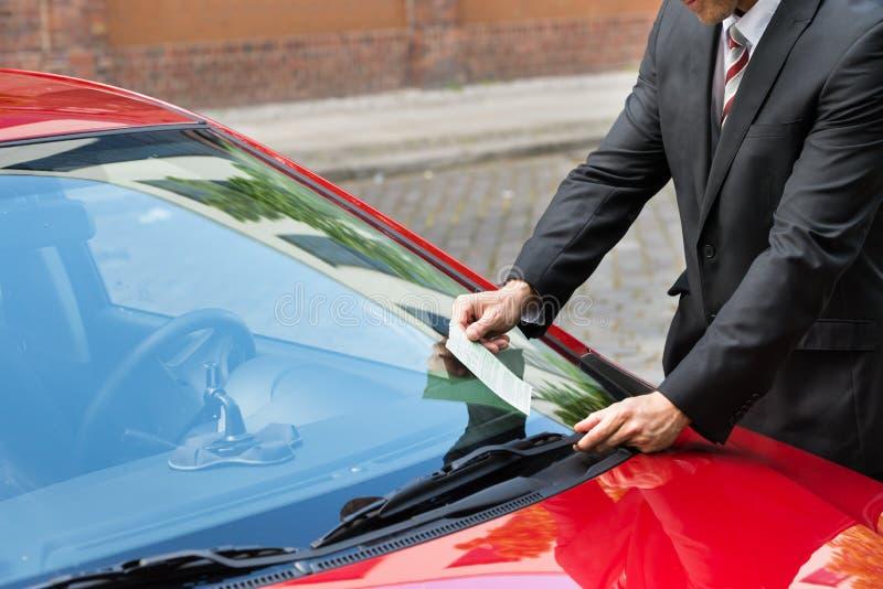 Homem que guarda um bilhete de estacionamento imagens de stock royalty free