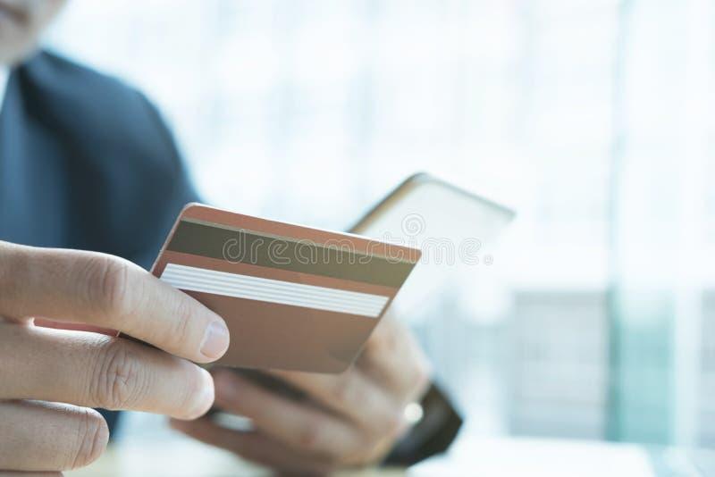 Homem que guarda um cartão de crédito e que usa o telefone celular esperto para o onli imagem de stock royalty free