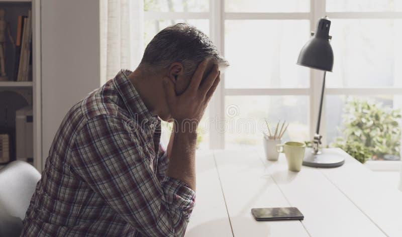Homem que guarda um smartphone e que espera uma chamada fotografia de stock