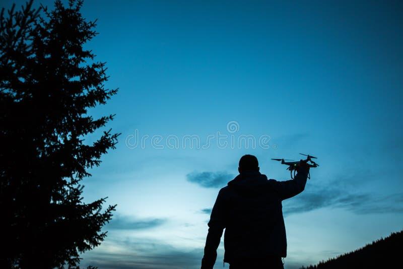 Homem que guarda um zangão para a fotografia aérea Silhueta contra t imagem de stock