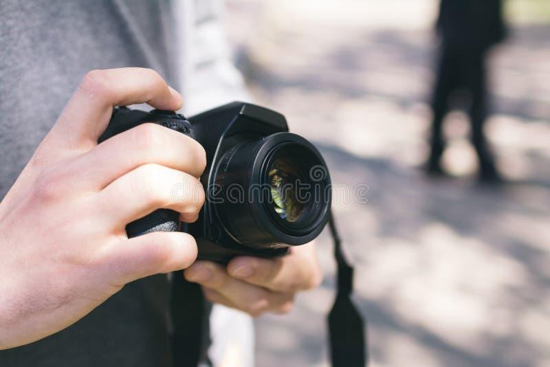 Homem que guarda uma câmera digital da foto fotos de stock royalty free