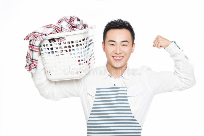 Homem que guarda uma cesta de lavanderia fotos de stock
